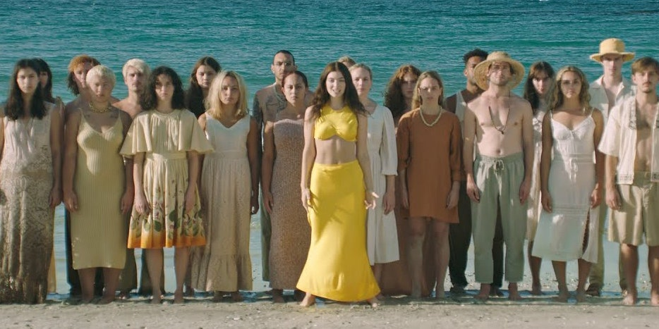 Group photo with singer Lorde in the middle wearing yellow